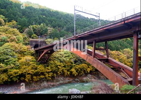 Iron railway bridge over Hozu River in Arashiyama, Japan - Stock Photo
