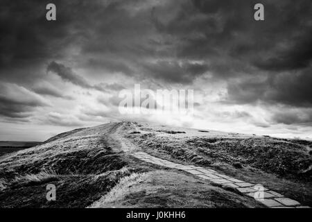 Stone path winds through Peak District moorland featuring rock formations on the horizon and large brooding sky - Stock Photo