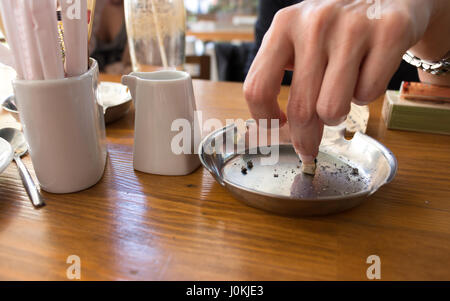 Hand putting out a cigarette in ashtray on a wooden table. - Stock Photo