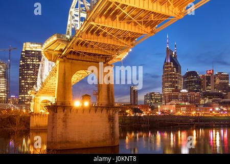 Twilight below the John Seigenthaler Pedestrian Bridge over the Cumberland River with skyline of Nashville, Tennessee, - Stock Photo