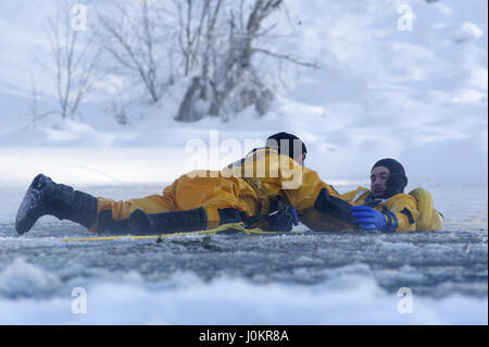 Air Force fire protection specialist, and Airman conduct ice water rescue training - Stock Photo