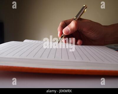 Hand with a pen writing on a page on a notebook. - Stock Photo