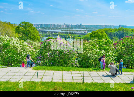 KIEV, UKRAINE - MAY 2, 2016: Locals climb to the top of the Botanical Garden hills to enjoy great view on beautiful - Stock Photo