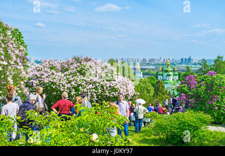 KIEV, UKRAINE - MAY 2, 2016: Visitors of Botanical Garden go inside lilac garden to enjoy aroma of flowers and great - Stock Photo