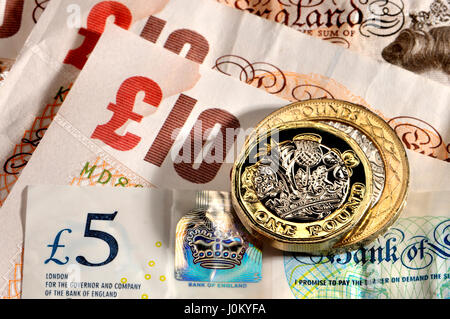 British pound coin - twelve-sided bimetallic 2017 release (dated 2016) with £2 coin, £5 polymer note and £10 notes - Stock Photo