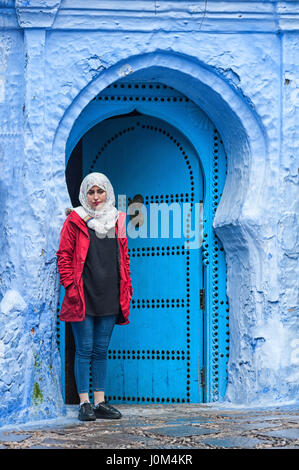 A woman in front of a typical moroccan door, in the blue Medina of Chefchaouen - Morocco - Stock Photo