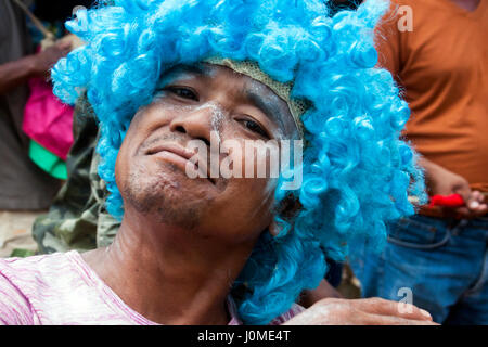A Cambodian man is wearing a blue wig while celebrating Khmer New Year in Chork Village, Tboung Province, Cambodia. - Stock Photo