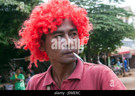 A Cambodian man is smoking a cigarette while wearing a red wig as he celebraties Khmer New Year in Chork Village, - Stock Photo