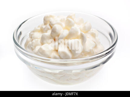 Fresh cottage cheese in glass bowl on white background - Stock Photo