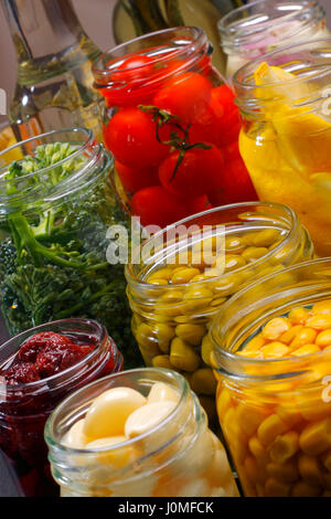 Opened jars in pantry with various preserved food. Oblique shoot. - Stock Photo