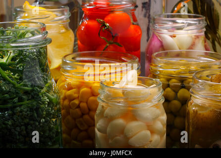 Opened jars in pantry with various preserved food - Stock Photo