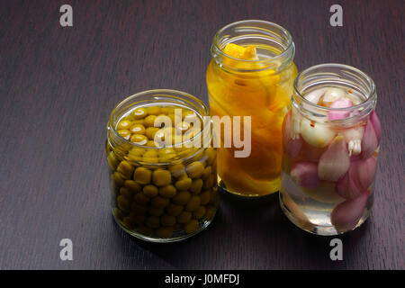 Three opened jars with green peas, onions and lemons on dark board. Copy space on left. - Stock Photo