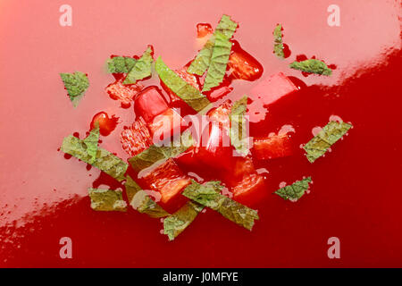 Close-up of cream tomato soup with chopped red pepper and green herbs - Stock Photo