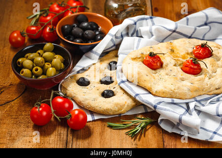 Traditional Italian Focaccia with tomatoes and olives and rosemary with olive oil on wooden table - Stock Photo