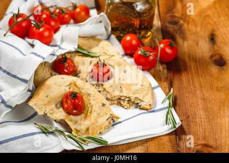 Traditional Italian Focaccia with tomatoes and rosemary with olive oil on wooden table - Stock Photo