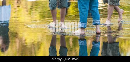 men walking barefoot through a puddle. - Stock Photo