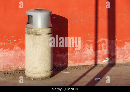 trash can trashcan dustbin garbage rubbish bins waste round outside in street against brick wall with brick copy - Stock Photo