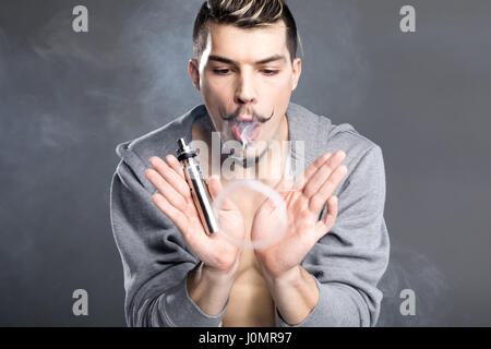 Young bearded man holding electronic cigarette and vaping on grey - Stock Photo