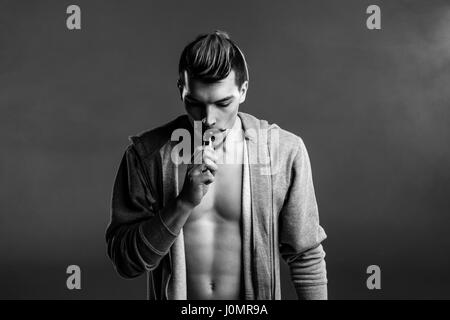 Black and white photo of young handsome man holding electronic cigarette and vaping - Stock Photo