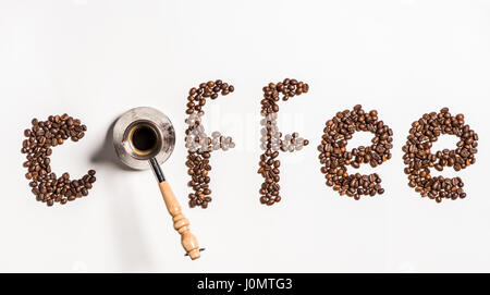 Top view of word coffee made from coffee beans and turkish coffee pot - Stock Photo