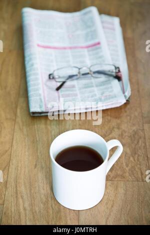 Tea over newspaper - Stock Photo