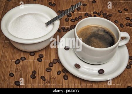 Fresh cup of coffee surrounded by coffee beans and sugar on a wooden background - cross pop filter - Stock Photo