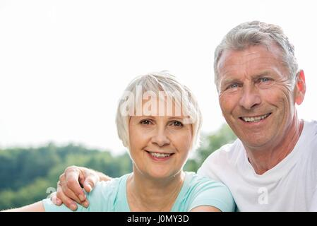 MODEL RELEASED. Senior couple smiling towards camera, man with arm around woman. - Stock Photo