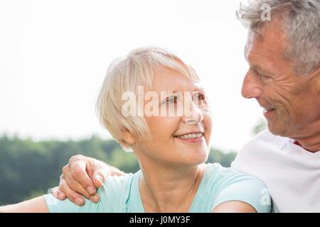 MODEL RELEASED. Senior couple smiling, man with arm around woman. - Stock Photo