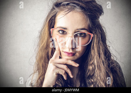 Brunette woman in glasses thinking - Stock Photo