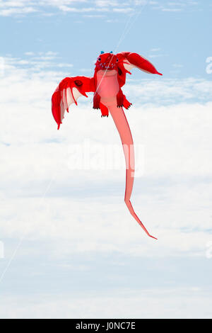 Semaphore, South Australia, Australia - April 15, 2017: Flying figure kite shaped as a red dragon at the Adelaide - Stock Photo