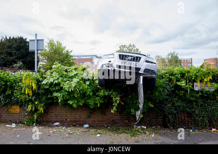 Wallington, Surrey, UK. 15th April, 2017. A car has crashed through a hedge in Shotfied carpark in Wallington, Surrey. - Stock Photo