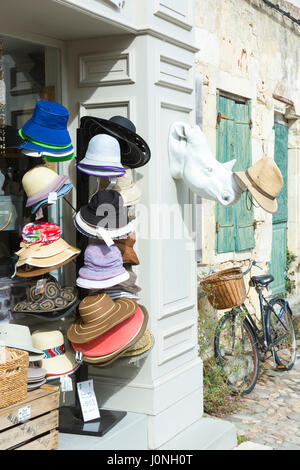 Typical street scene quaint house with shutters and hats on sale in gift shop in St Martin de Re, Ile de Re, France - Stock Photo