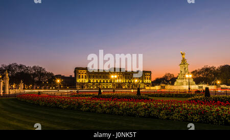 Lights at dusk and red skies over Buckingham Palace, London, UK - Stock Photo