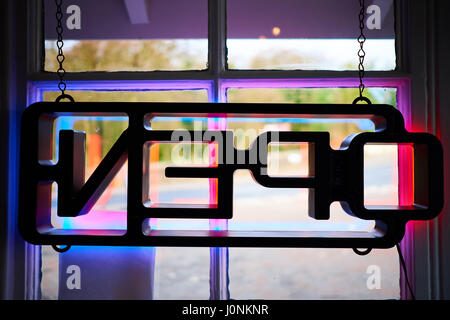 Lit up neon multicoloured Open sign hung in diner window seen from reverse looking outward. - Stock Photo