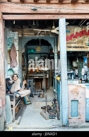 Shopkeeper smoking, resting in a repair shop for old-fashioned vintage hand cranked sewing machines, Pragpur heritage - Stock Photo