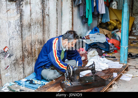 Local Indian man working as a tailor using an old fashioned sewing machine at a roadside shop in Pragpur heritage - Stock Photo