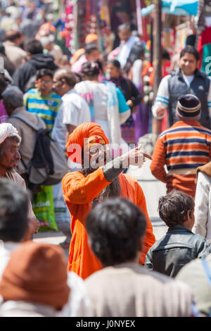 BADRINATH  INDIA, JUNE 5th - A sadhu amongst pilgrims on the streets near the temple of Badarinath in North India - Stock Photo
