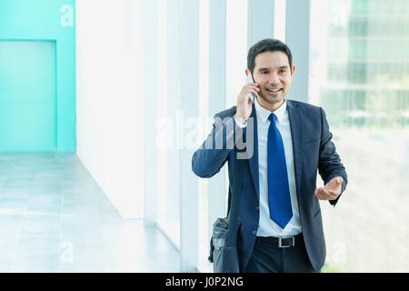 Business man walking and using mobile phone to chatting with friend after work at corridor office building. - Stock Photo