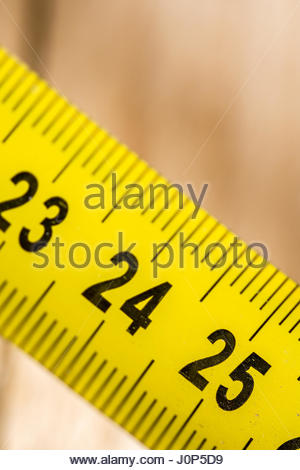 Yellow metal meter on the wooden planks background. - Stock Photo