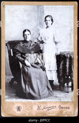 Tambov, Russian Federation - March 29, 2015 Vintage photograph of two women in photo studio. Old woman sitting on - Stock Photo