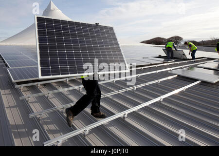 Solar pv being installed onto the roof of Truro college - Stock Photo