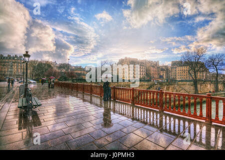 Lovers in the rain on the Pont au Double. France. Paris - Stock Photo