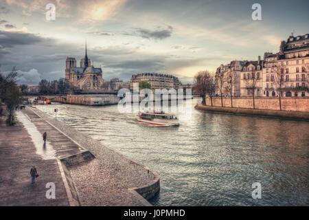 Tourist ship and Cathédrale Notre-Dame de Paris on Île de la Cité. Paris. France - Stock Photo