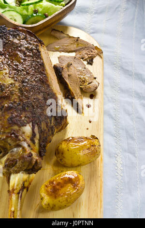Roasted leg of lamb with potatoes and salad - Stock Photo