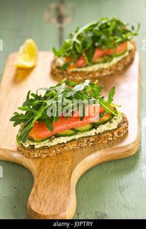 Open face sandwich with cottage cheese, cucumber, rucola and smoked salmon - Stock Photo