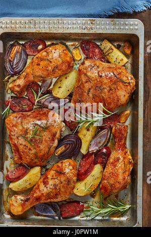 Spanish chicken tray bake with chorizo, potatoes and red onion - Stock Photo