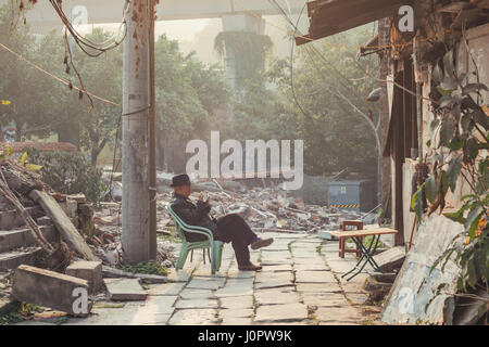 25,Dec, 2015,China,Chongqing : a man sitting  on a chair in front of bricks and undevelopment place beside the famous - Stock Photo