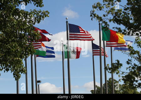 The flags US, Nepal, Cameroon,  Israel, India, Mexico and Cuba on a flagpoles blowing in the wind against a blue - Stock Photo