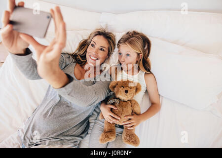 Mother and daughter lying on bed and taking self portrait with mobile phone. Woman taking selfie with a little girl - Stock Photo