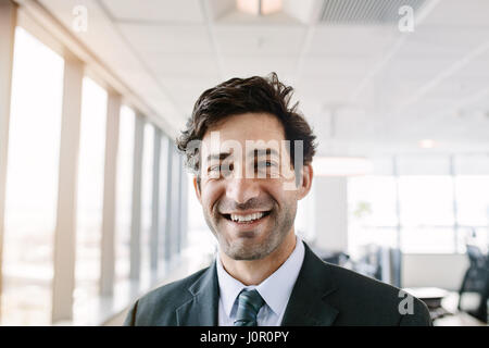 Portrait of successful young businessman standing in office. Manager in suit looking at camera with a smile. - Stock Photo